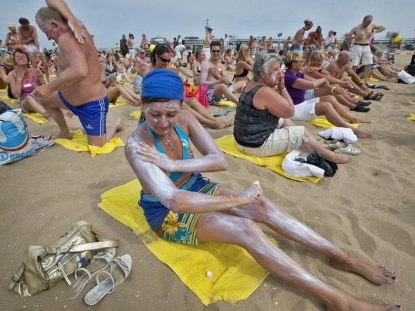 A woman applies sunscreen on her body on a beach in the Netherlands.