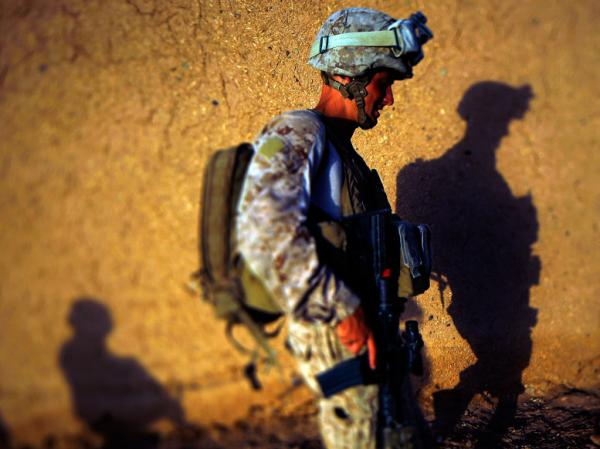 Darryl St. George, a Navy Corpsman with Weapons Co. 2/8 Marines out of Camp Lejeune, North Carolina, walks along  a mud compound wall with Afghan National Army soldiers while on a foot patrol in Northern Marja, Helmand Provence, southern Afghanistan.