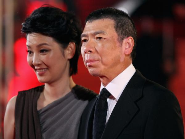 Director Feng Xiaogang, whose 2010 film <em>Aftershock</em> is China's highest-grossing Chinese-made film of all time, arrives at the 14th Shanghai International Film Festival. At left is his wife Xu Fan, who starred in <em>Aftershock.</em>