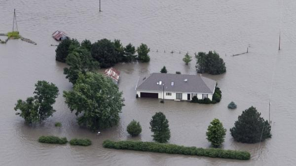 The rising Missouri River swallows a home in Hamburg, Iowa, this week.
