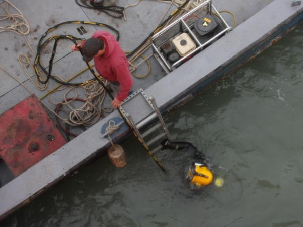 Chad Stephens helps diver Tom Warvell to recover an ice sensor from the bottom of Lake Erie. The two are part of a company (specializing in underwater recovery) working with engineers studying how ice floes during the winter would affect the foundation of a lake-based wind turbine.