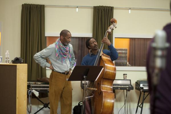 Ron Carter (left, as himself) looks on as Albert Lambreaux (Clarke Peters) attempts to show him a thing or two on bass, in <em>Treme</em>.