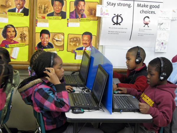 Kindergartners at KIPP Empowerment Academy in South Los Angeles work on laptops while in another corner of the room, a group of students do an activity with a teacher.