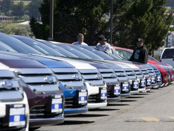 A salesman looks at Ford Fusion cars with customers on the lot at the Serramonte Ford dealership in Colma, Calif. This year, Ford Motor Co. reported its best first-quarter earnings since 1998, at $2.6 billion.