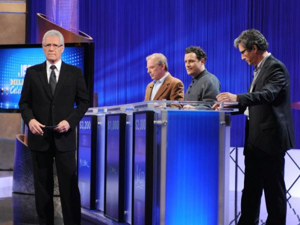 Host Alex Trebek greets celebrity contestants on the set of <em>Jeopardy!</em> For non-celebrity contestants, fame means a 30-second personal anecdote after the first commercial break.