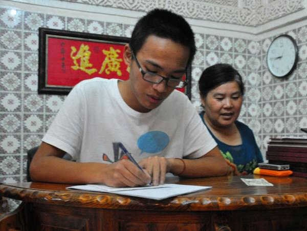 Dai Songxian (right) and her son,  Alex, take a food order. They run the only remaining Chinese restaurant in  Tripoli, as fighting has caused other foreigners to flee.