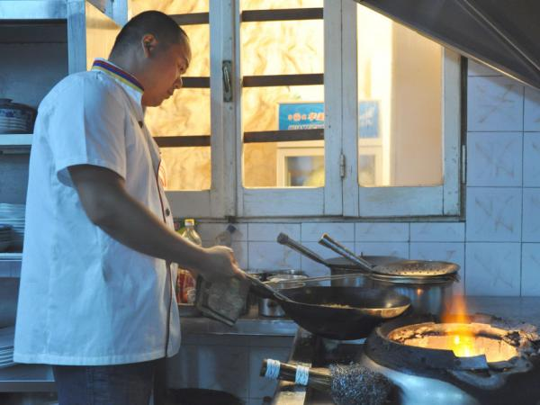 Chef Lao Wei Xiong cooks up a carry-out order for foreign reporters in the  kitchen at al Maida restaurant in Tripoli.