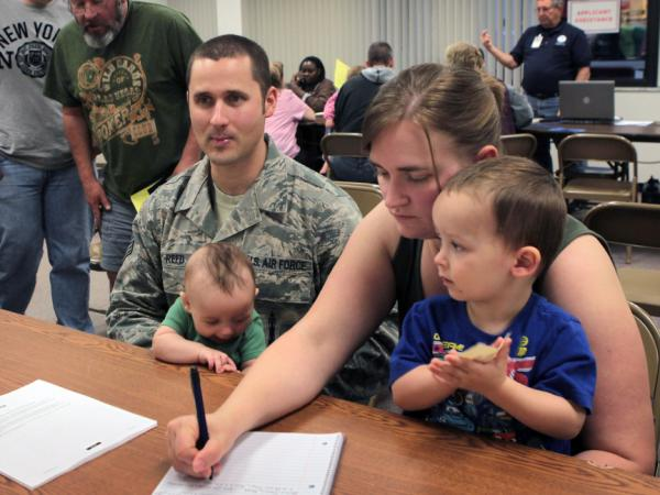 Air Force SSgt. Chris Reed, holding his son Colby, and his wife, Tracy, with son Wesley, seek help at the FEMA office. The couple is looking for housing after their home flooded.