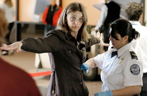 A Transportation Security Administration agent performs a pat-down check on an airline passenger at a security checkpoint at Phoenix Sky Harbor International Airport.