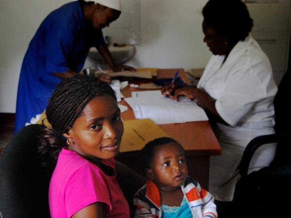 Lucrecia Silva and her daughter, Helena, are both HIV-positive. They wait as a nurse in Macia writes a prescription for Helena's anti-retroviral drugs.
