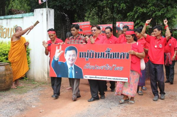 "A Buddhist monk sprinkles holy water on Red Shirt leaders  as they parade through Baan Suksomboon in northeastern Thailand's Udon  Thani province. Baan Suksomboon is  Thailand's 255th  Red Village to declare its support for  opposition candidate Yingluck Shinawatra. Thaksin Shinawatra, pictured on the  campaign poster, jokingly calls his sister his ""clone."""