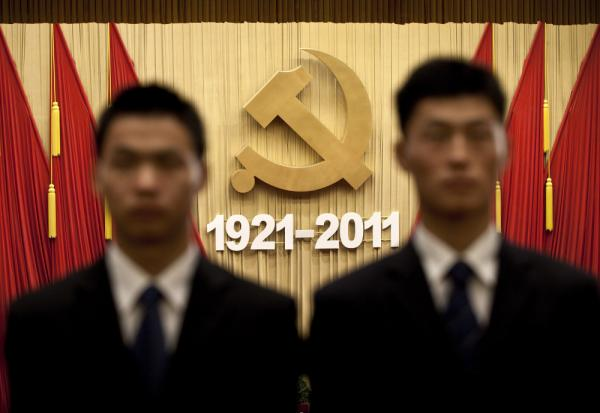 Chinese security officers stand against the Communist Party's emblem while singing a patriotic song during the celebration of the party's 90th anniversary at the Great Hall of the People in Beijing, China, Friday, July 1, 2011.