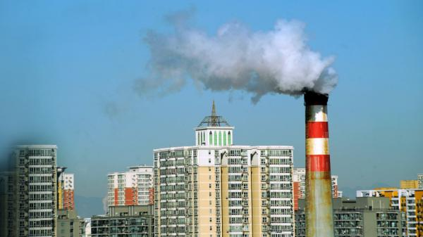 Pollutants billow out of a chimney amid a group of residential housings in Beijing.