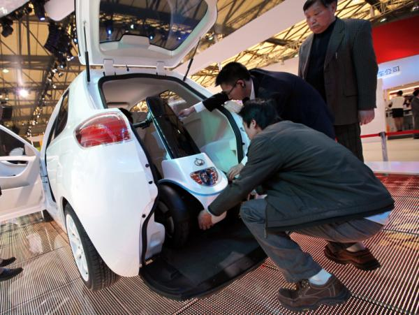 Workers set an electric moped into the back of a McCar, a new Geely's concept car, at the Shanghai International Auto Show on Wednesday, April 20, 2011 in Shanghai.