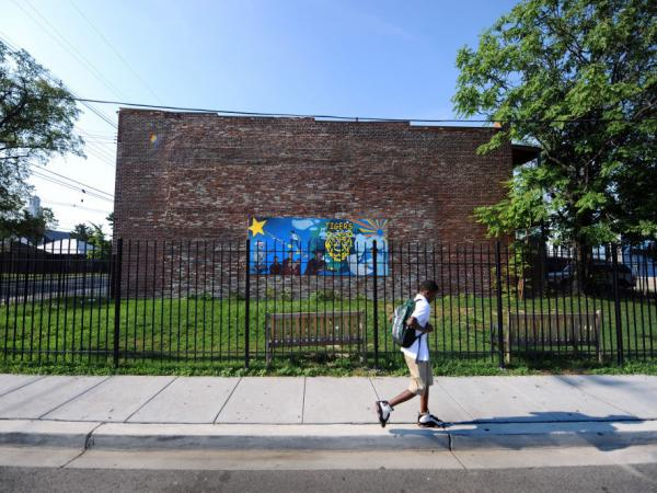 A boy walks to school past a mural in a fenced off and locked lot along Martin Luther King Jr. Avenue Southeat in the poorest ward of the city on July 23, 2010 in the Anacostia section of Washington.