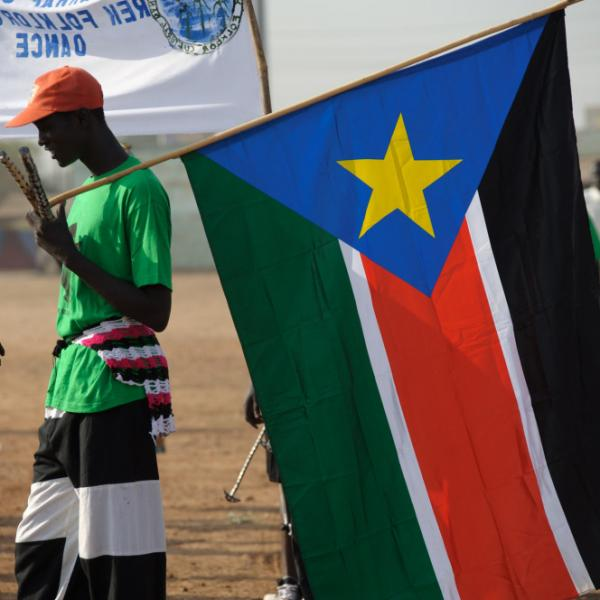 A Sudanese man holds the flag of South Sudan.