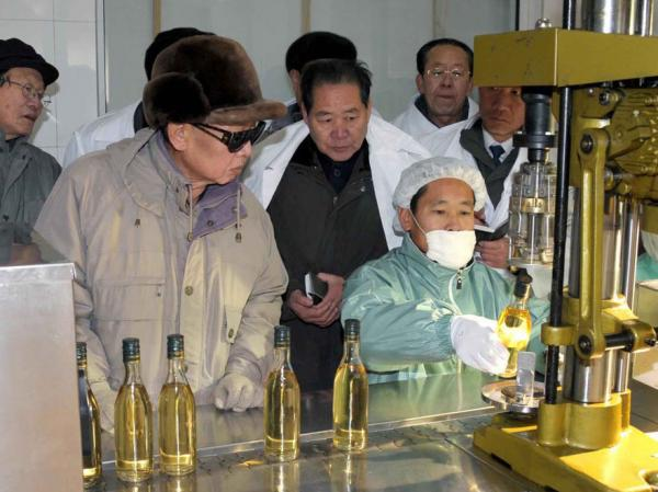 In this undated photo released by Korean Central News Agency via Korea News Service in Tokyo December 2009, North Korean leader Kim Jong Il, left, looks at a bottle containing an alcoholic beverage as he visits a factory of the Rason Taehung Trading Company in North Hamgyong Province, North Korea.