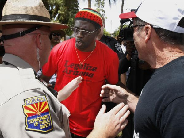 "A police officer, left, tries to keep the peace as immigrant rights protester Bobby DeVeaux, middle, and ""Tea Party"" supporter David Jones, right, argue as 450 immigrant rights protesters march on the Arizona Capitol last spring."