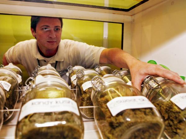 Ryan Cook reaches for a jar of medical marijuana at one of his clinics in Denver, Colo. on June 24.
