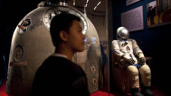 A visitor stands near the Shenzhou 5 re-entry capsule that was used in China's first human spaceflight mission, and the space suit worn by crew member Yang Liwei at an exhibition in Beijing on July 6.