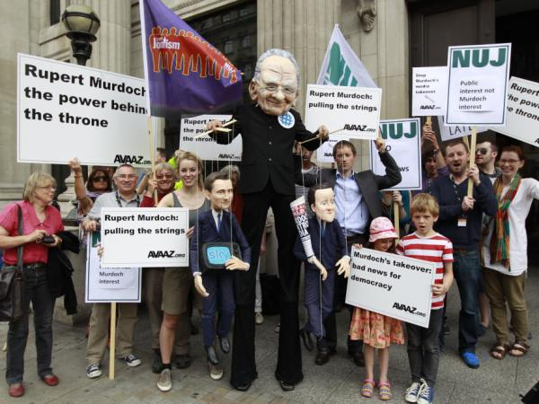 Demonstrators, one wearing a mask depicting Rupert Murdoch, center, holds puppets depicting British Prime Minister David Cameron (right) and British Culture Minister Jeremy Hunt (left) as they protest outside the Department of Culture Media and Sport in central London on Thursday to show their opposition to the proposed sale of BSkyB to Murdoch's News International.