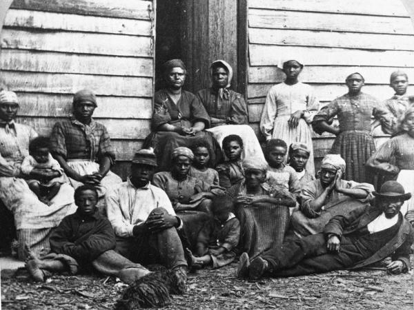 Civil War fugitive slaves who were emancipated upon reaching the North, sitting outside a house, possible in Freedman's Village in Arlington, Virginia, mid 1860s.