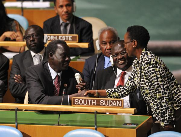 The South Sudan delegation, including Vice-President Riek Machar Teny-Dhurgon (second from right), are congratulated by a delegate as they take their seats after the U.N. General Assembly voted to admit the newly formed nation.