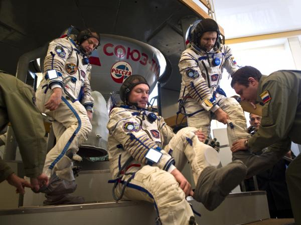 Crew members of the International Space Station, (from left) U.S. astronaut Ron Garan, Russian cosmonauts Alexander Samokytyaev and Andrei Borisenko, prepare to enter a Soyuz simulator outside Moscow on March 30, 2011. With the space shuttle out of commission, the Russian Soyuz vehicle will be the only way for Americans to reach space.