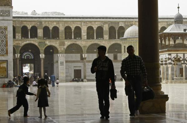 Syrians walk outside the Omayyad Mosque in the old city Damascus in April. Residents are adapting to life amid the s ongoing uprising against President Bashar Assad's regime.