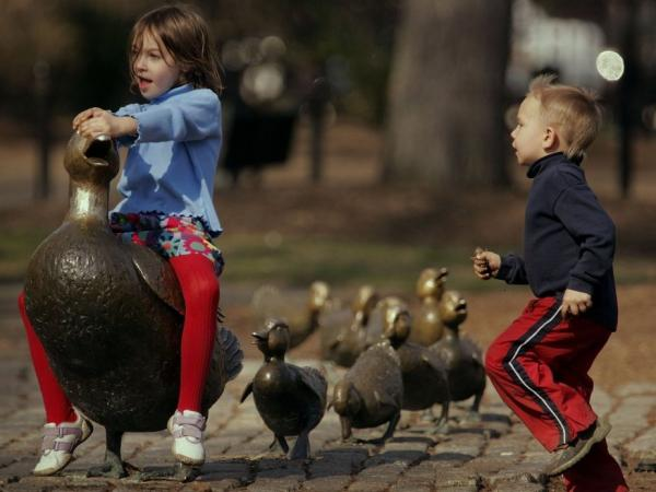 Brianna Henderson and her brother Ian Henderson play on the <em>Make Way for Ducklings</em> statues in Boston. The bronze figures by sculptor Nancy Schön were installed in Boston's Public Garden in 1987.