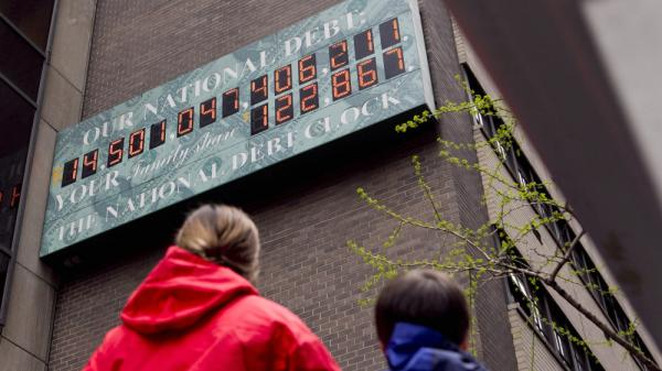 Pedestrians stop to view the National Debt Clock in New York this April. The debt ceiling is becoming an election issue, as groups on both sides spend millions on TV ads.