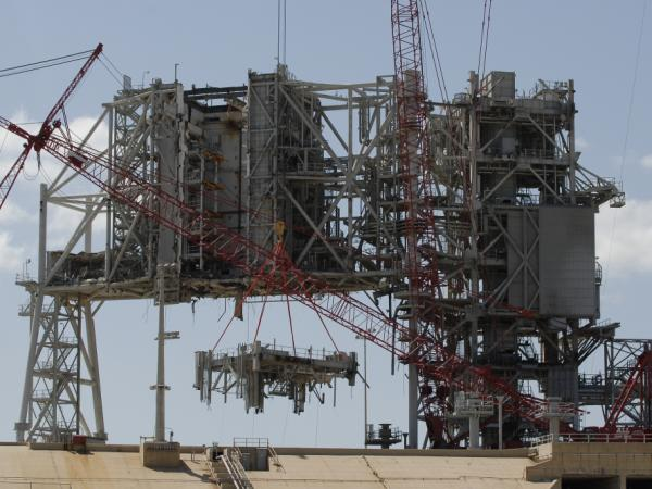 Cranes deconstruct a large section of the structure used to launch the space shuttles at launch pad 39B at Kennedy Space Center on April 6.