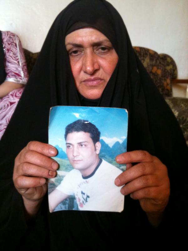 Umm Haidar holds a photograph of her missing son, Haidar.