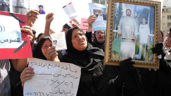 Women hold photographs and signs of their missing male relatives during a weekly protest in Baghdad's Tahrir Square.