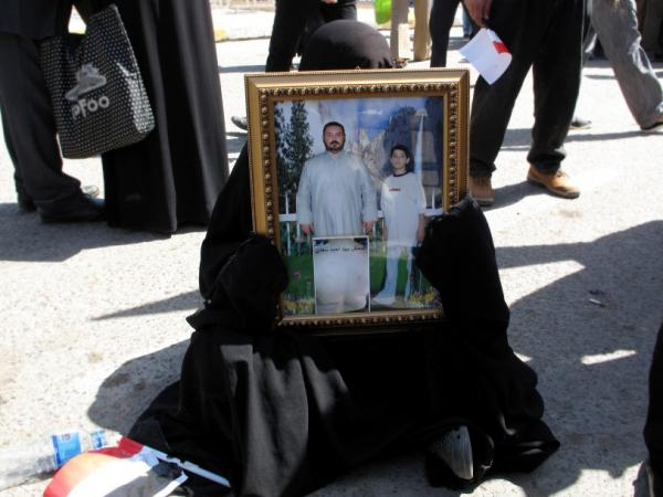 A woman at the protest holds a photograph of missing male relatives.