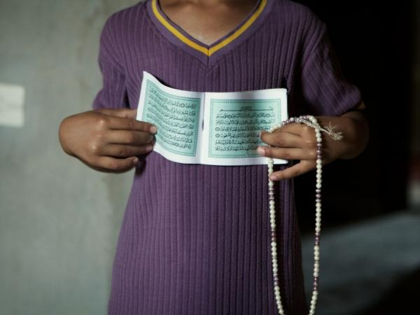 A Zintani family had been living in Tripoli but fled because of violence and instability in the capital. Here, one of the children shows the family's Quran and prayer beads, two of the few possessions they brought with them from Tripoli.