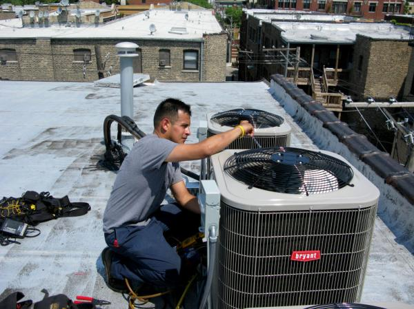 "Eric Rebolledo, a repairman for AllTemp heating and air conditioning in Chicago, works on an air-conditioning unit on the roof of an apartment building. ""I don't remember it being this hot for at least 10 years that I can recall,"" he says. ""This is unusual, man, so it's gonna create some havoc with the air-conditioning  systems."""