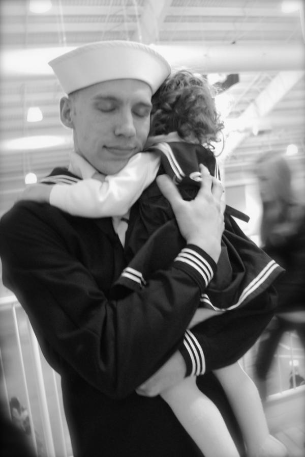 Justin Bock holds his daughter, Lina, at his graduation from basic training earlier this year. Bock decided to enlist in the Navy after both he and his wife, Ashley, were laid off.