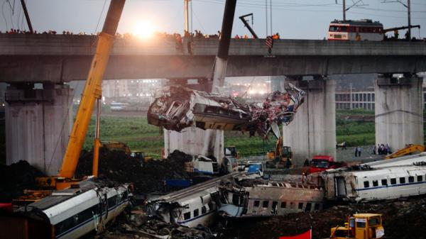 A wrecked train carriage is lifted from the scene of a crash Saturday involving two trains in Wenzhou, in China's Zhejiang province.