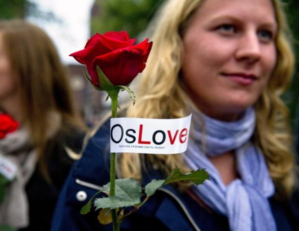 "Two women carry roses tagged with the slogan ""OsLove"" as they joined as many as 150,000 people gathered for a flower vigil in Oslo."
