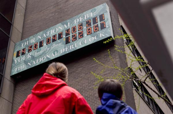 Pedestrians stop to view the National Debt Clock in New York this April.