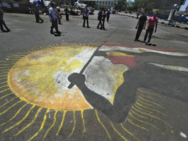 People in Tahrir Square walk by graffiti showing a protester with an Egyptian flag in front of the sun on Saturday.