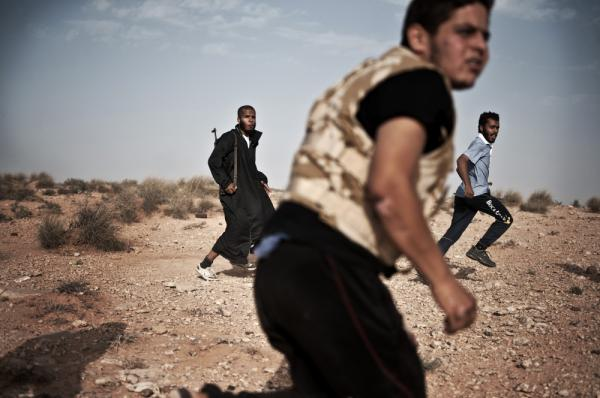 Libyan rebel fighters run for cover at the front line near the southwest desert town of Gualish on July 24, as Gadhafi forces started attacking them in an attempt to capture the city.