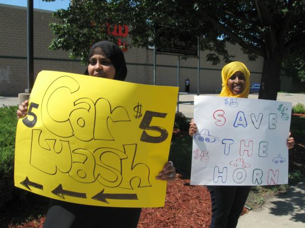 Iman Warsame (left) and Fardosa Ahmed drum up business for their car wash; proceeds from the event (below) went to help drought victims in Somalia.