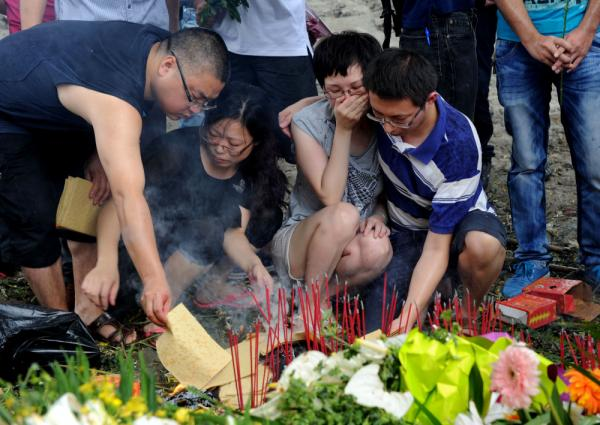 Family members lighting and leaving sticks of incense as they mourn victims who died in the July 23 high-speed train crash at the accident scene in Shuangyu, near Wenzhou.