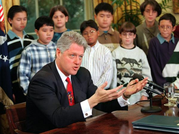 President Clinton, accompanied by sixth grade students from Thomas Jefferson Middle School in Arlington, Va., gestures while speaking in the Oval Office of the White House Monday Dec. 18, 1995 after vetoing two spending bills. With negotiators mired in a broader budget debate, the president vetoed the bills arguing they would undermine the nation's environment.