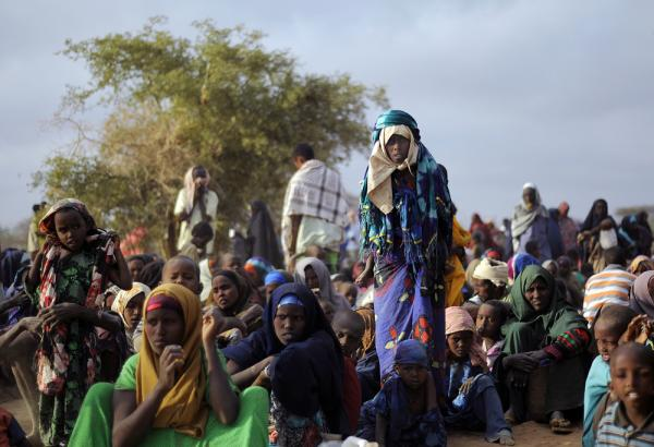 Somali refugees wait at dawn at a registration center at the Dadaab refugee complex in Kenya Tuesday, to receive aid after having been displaced from their homes in southern Somalia by famine.