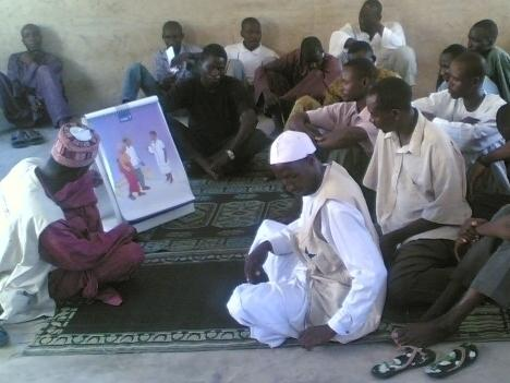 Abubakar Rigasa, a peer educator, discusses family planning options with a group of men in Kaduna State, Nigeria.