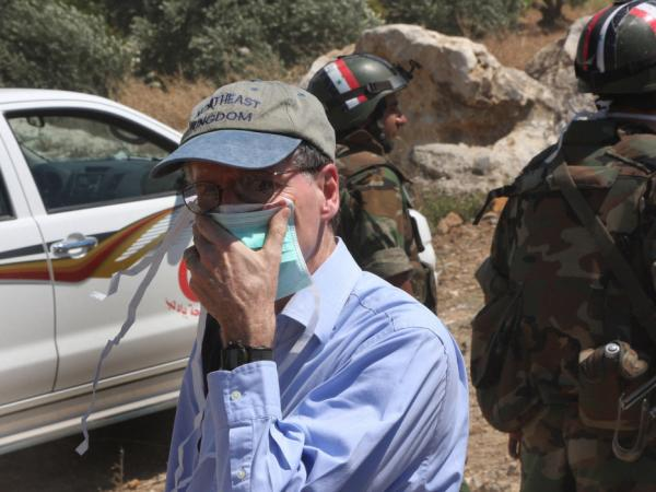 In this photo taken during a government-organized tour for  foreign diplomats and the media, US ambassador to Syria Robert Ford covers his nose from the smell of the dead bodies during his visit with other foreign diplomats to a mass grave, in Jisr el-Shughour, north of Syria, on Monday, June 20, 2011.