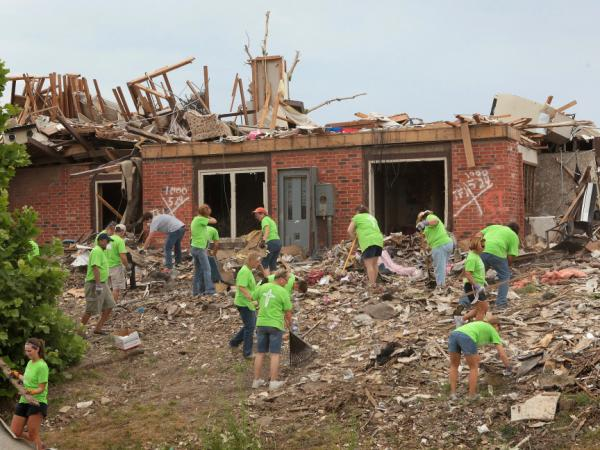 Volunteers clear debris from a tornado-damaged apartment complex late last month, two months after a tornado ripped through town, killing 160 people and destroying a third of the city.